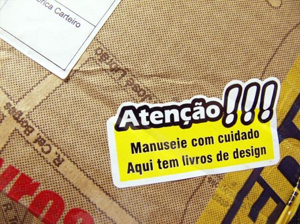 """Selo """"Atenção! Manuseie com cudado. Aqui tem livros de design"""", nas embalagens da Editora 2AB"""